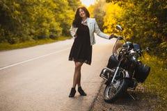 Attraktive brunette Motorradfahrerstellung nahe einem Motorrad auf dem Sonnenuntergang lizenzfreie stockfotos