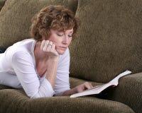 Attraktive Brunettefrau, die auf Couch mit Buch sich entspannt Lizenzfreie Stockfotografie