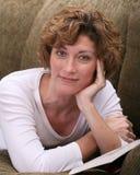 Attraktive Brunettefrau, die auf Couch mit Buch sich entspannt Stockbilder