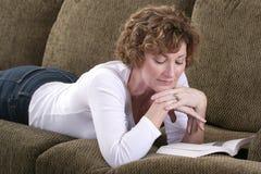 Attraktive Brunettefrau, die auf Couch mit Buch sich entspannt Lizenzfreies Stockbild
