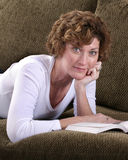 Attraktive Brunettefrau, die auf Couch mit Buch sich entspannt Stockfotos