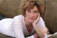 Attraktive Brunettefrau, die auf Couch mit Buch sich entspannt Stockfoto