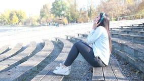 Attraktive Brunettefrau, die Musik mit Kopfhörern am Park hört stock video