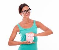Attraktive Brunettefrau, die Sparschwein hält Lizenzfreie Stockfotos