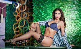 Attraktive Brunettefrau mit den langen Beinen in der Wäsche und in schwarzen Strümpfen, die auf Stange in einem Nachtklub legen H Stockfotos