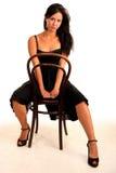 Attraktive Brunettefrau sitzt auf Stuhl Lizenzfreie Stockbilder