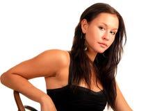 Attraktive Brunettefrau sitzt auf Stuhl Stockbild