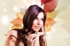 Attraktive Brunettefrau vor einem abstrakten Hintergrund Stockfoto