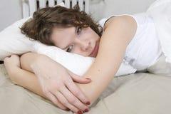 Attraktive Brunetterotationfrau, die auf dem Bett liegt Stockfotografie