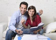 Attraktive Couch der Paarbuchhaltungs-Schuld zu Hause glücklich im Finanzerfolg und im Reichtum Stockbilder