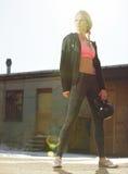 Attraktive Crossfit-Frau, die ein Kettlebell hält Stockfoto