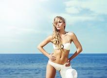 Attraktive, dünne Frau im anziehenden Bikini, der mit einem Hut auf t aufwirft Lizenzfreie Stockfotos