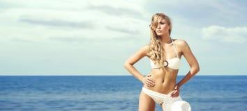 Attraktive, dünne Frau im anziehenden Bikini, der mit einem Hut auf t aufwirft Stockfotos