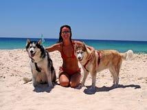 Attraktive Dame auf sonnigem Strand mit weißem Sand und blauen Himmeln, mit zwei schönen blauen gemusterten Hunden Lizenzfreie Stockfotografie