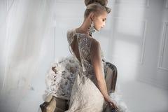 Attraktive Dame, die ein weißes Luxuskleid trägt Stockbild