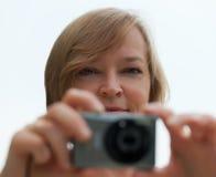 Attraktive Dame, die Foto mit Digitalkamera nimmt. Stockbilder