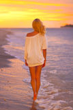 Attraktive Dame am tropischen Strand im Sonnenuntergang. Stockbild