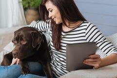 Attraktive Dame und ihr Haustier, die gemütlichen Wochenendenmoment teilt Lizenzfreies Stockfoto