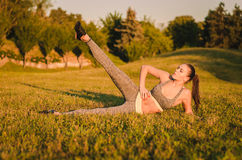 Attraktive Eignungsfrau, die auf dem Gras im Park und im doin liegt Stockbild