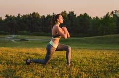 Attraktive Eignungsfrau, die im Park auf dem Gras übt Es Lizenzfreie Stockfotos