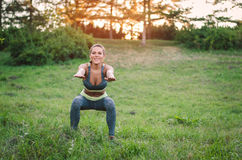 Attraktive Eignungsfrau, die im Park auf dem Gras übt SH Lizenzfreie Stockfotos