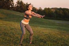 Attraktive Eignungsfrau, die im Park auf dem Gras übt SH Stockfotografie
