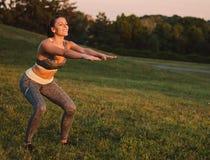 Attraktive Eignungsfrau, die im Park auf dem Gras übt SH Lizenzfreies Stockbild