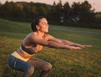Attraktive Eignungsfrau, die im Park auf dem Gras übt SH Stockbilder
