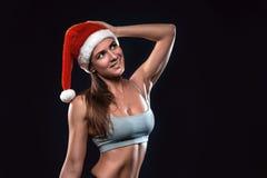 Attraktive Eignungsfrau steht im Weihnachtshut und schaut aufwärts stockbild