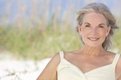 Attraktive elegante ältere Frau, die an einem Strand sitzt Stockfoto
