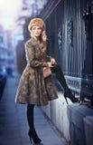 Attraktive elegante blonde junge Frau, die eine Ausstattung mit russischem Einfluss im städtischen Modeschuß trägt. Schönes modern Stockfotografie