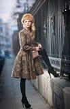 Attraktive elegante blonde junge Frau, die eine Ausstattung mit russischem Einfluss im städtischen Modeschuß trägt. Schönes modern Stockfoto