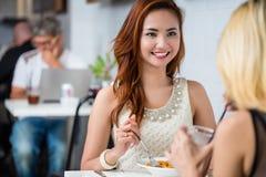 Attraktive elegante Frau, die mit einem Freund zu Mittag isst Lizenzfreies Stockbild