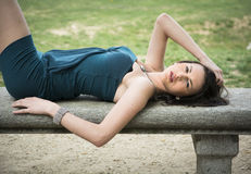 Attraktive elegante junge Frau auf Steinbank Stockfoto