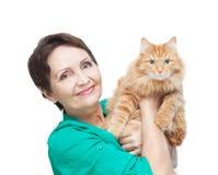 Attraktive emotionale Frau 50 Jahre alt mit der roten Katze an lokalisiert Stockbilder