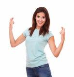 Attraktive erwachsene Frau, die ihre Finger kreuzt Stockfoto