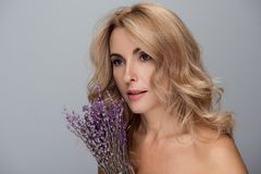 Attraktive erwachsene Frau hält Blumen Lizenzfreies Stockbild