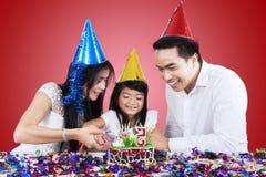 Attraktive Familie, die einen Geburtstagskuchen schneidet lizenzfreie stockfotos