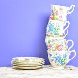Attraktive feine Teeschalen des feinen Porzellans auf einem purpurroten Hintergrund Stockfoto