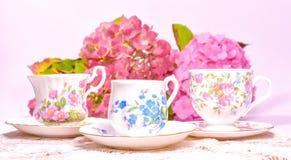 Attraktive feine Teeschalen des feinen Porzellans auf einem rosa Hintergrund lizenzfreies stockfoto