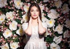 Attraktive Frau auf Blumenhintergrund im Studiofoto lizenzfreie stockfotografie