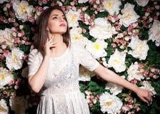 Attraktive Frau auf Blumenhintergrund im Studiofoto stockfotos