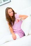 Attraktive Frau auf dem Sofa, das Borduhr betrachtet Lizenzfreies Stockfoto
