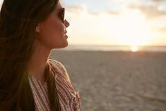 Attraktive Frau auf dem Strand bei Sonnenuntergang Stockbilder