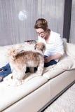 Attraktive Frau auf der Couch, die ihren Hund einzieht Stockfotografie