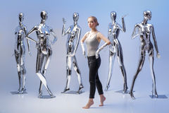 Attraktive Frau auf Hintergrund von vielen metallisches glänzendes Mannequin Stockfotos