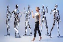 Attraktive Frau auf Hintergrund von vielen metallisches glänzendes Mannequin Lizenzfreies Stockfoto