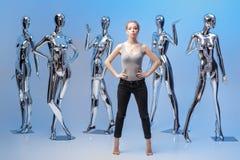 Attraktive Frau auf Hintergrund von vielen metallisches glänzendes Mannequin Stockfoto