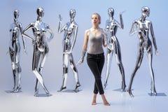 Attraktive Frau auf Hintergrund von vielen metallisches glänzendes Mannequin Lizenzfreie Stockfotografie