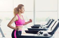 Attraktive Frau auf Tretmühle im Fitness-Club, gesunder Lebensstil Stockfotografie